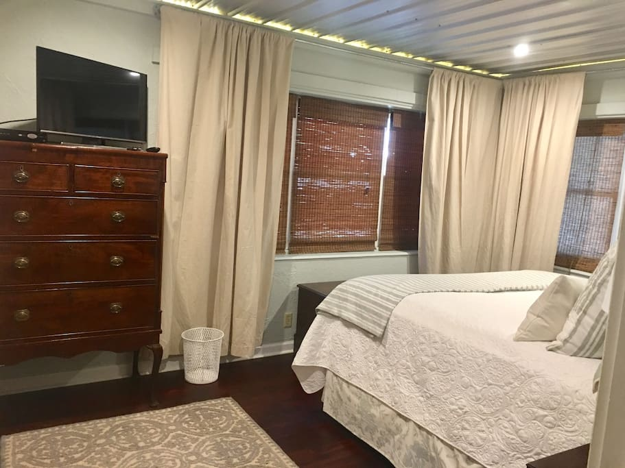 First bedroom with one king bed. Amenities include spacious closet, dresser and television.