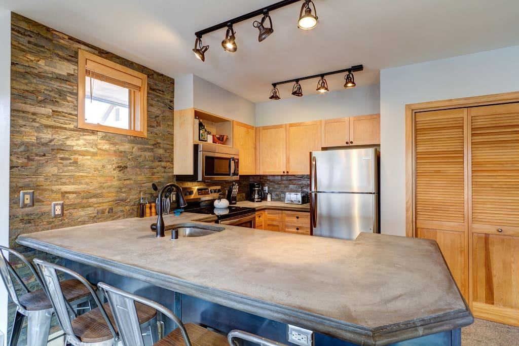 Our beautiful kitchen features brand-new stainless steel appliances, custom-crafted concrete countertops, and a shimmering slate backsplash.