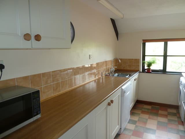 Kitchen with microwave, cooker, dishwasher and fridge freezer