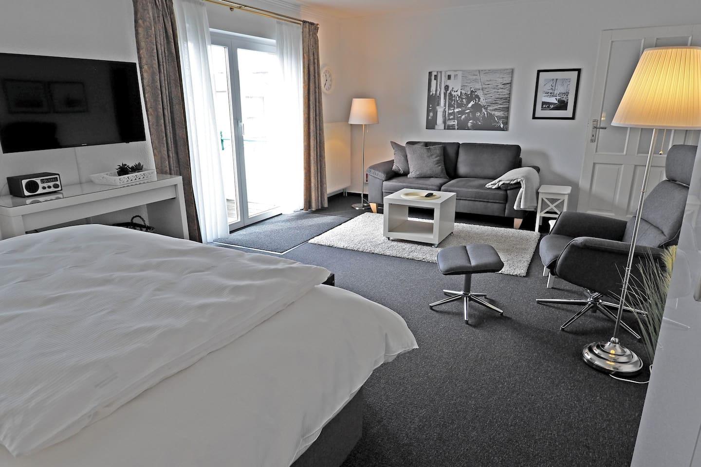 """Wohn-/Schlafzimmer mit Sessel, Sofa, Radio und 43"""" 4k UHD Sat TV"""