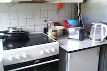 Kitchen has stove, refrigerator, toaster and electric kettle.