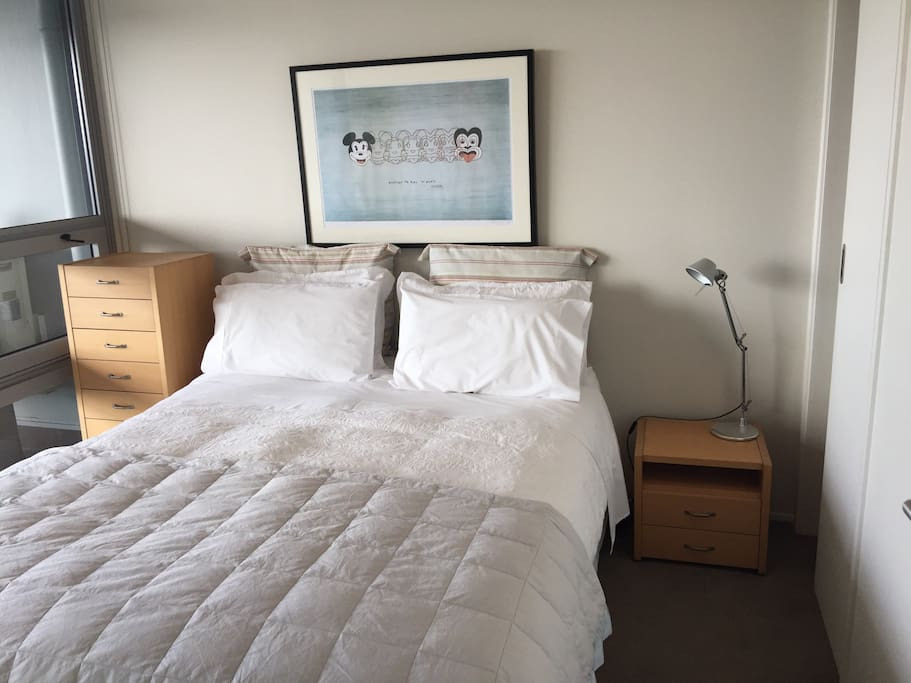 Your bedroom with queen bed , wardrobe, dressing gowns, suitcase stands and doors open onto deck