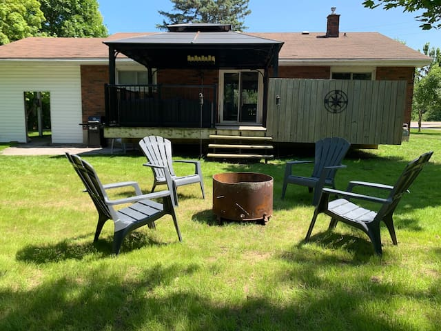 Backyard with propane bbq, patio area and fire pit (bring your own wood) and large deck with set-in private hot tub and outdoor seating under gazebo