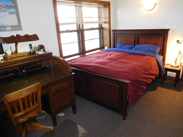 Large walkout level bedroom with queen bed and antique roll top desk. Also a great view of the lake from the bed.  Walkout access to patio overlooking lake.  Private bath in lower level.