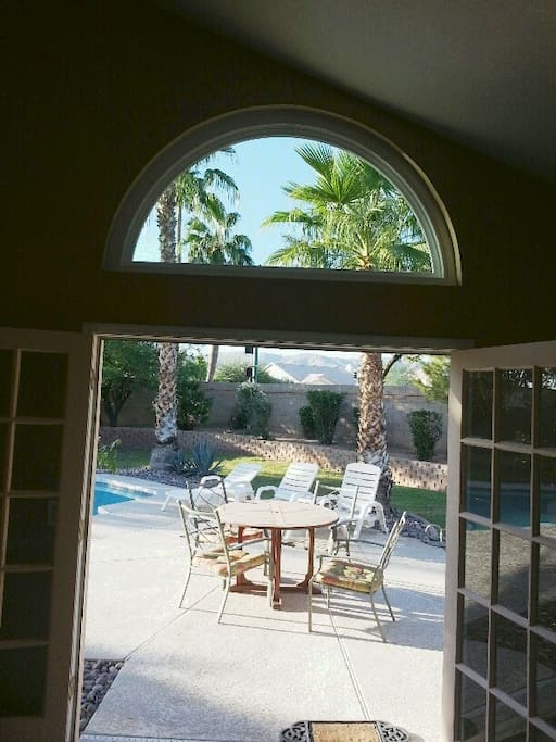 View from master bedroom out on to pool deck and huge back yard
