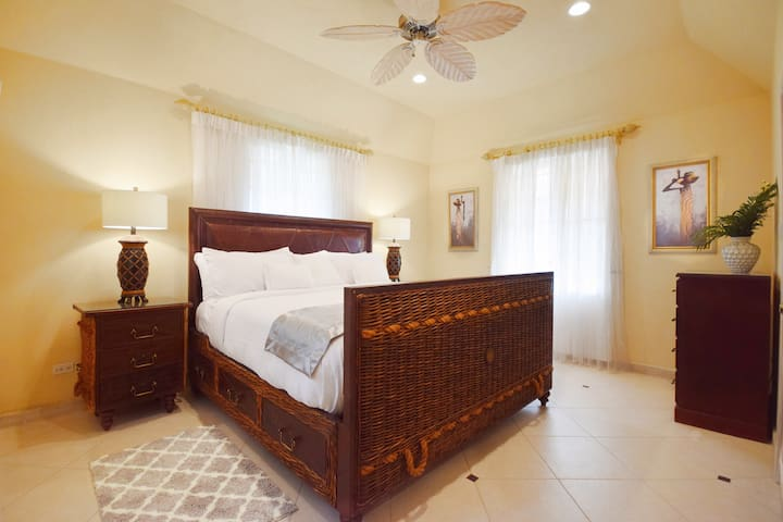 The master king bedroom on the upper floor with a/c, ceiling fan and en suite bathroom