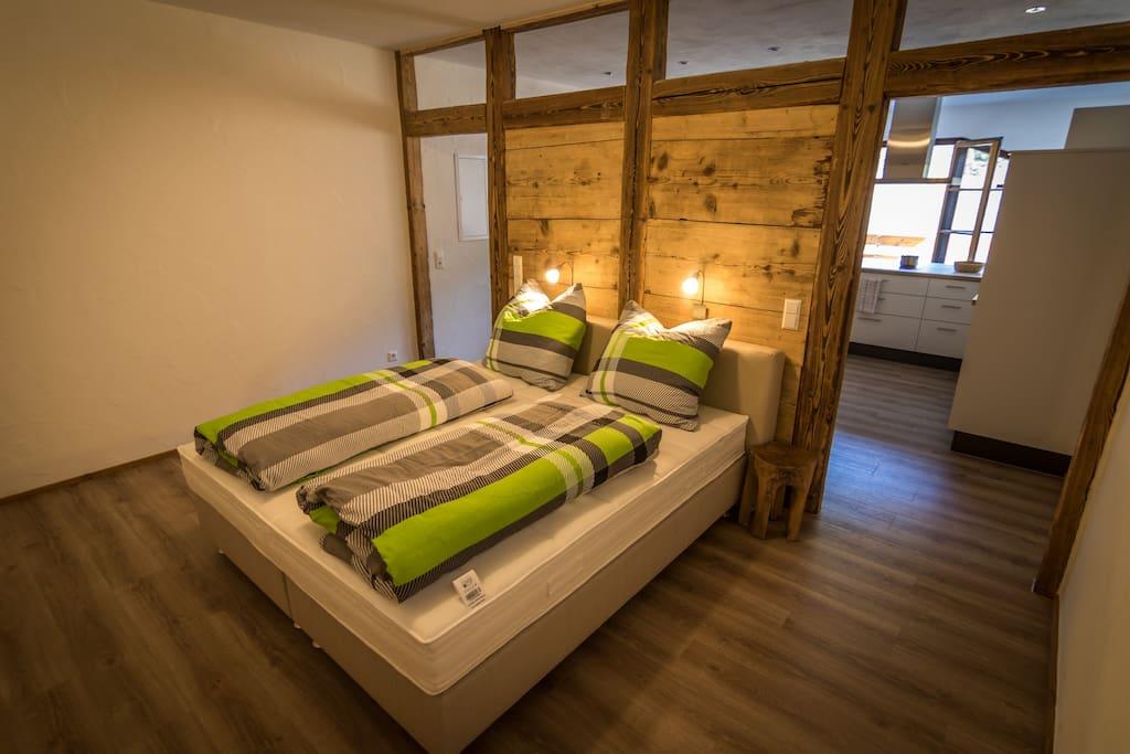 Schlafbereich abgetrennt durch einen Raumteiler in Massiv-Altholz