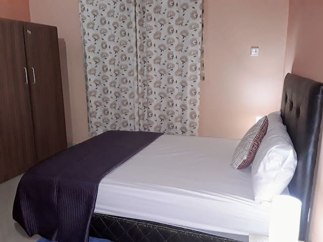 Bedroom 3: Ensuite bedroom fitted with a double bed, wardrobe, air conditioner, ceiling fan, bedside unit and lamp