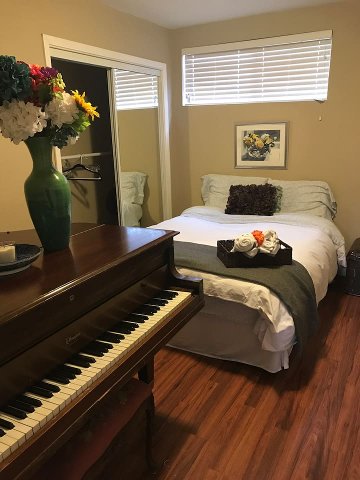Baby grand piano and a full memory foam bed