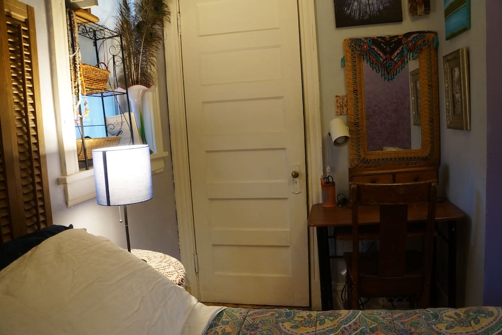 Bedroom door leading to kitchen, small desk with lamp