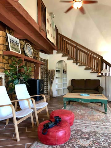 """Our open space living room, with twin size sofa bed and pellet stove to warm up on those chilly winter nights. Small """"Harry Potter"""" room under the stairs makes a perfect little library and office.."""