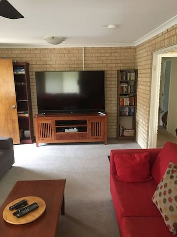 """Lounge room with 75"""" TV, Apple TV, Foxtel Now & DVD player."""