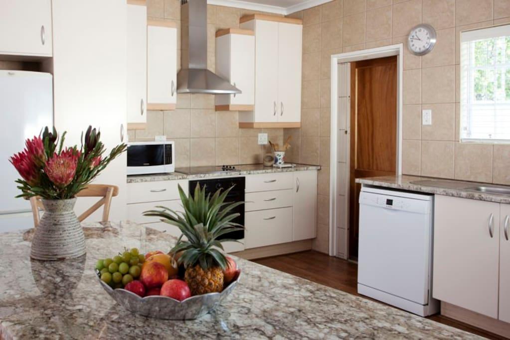 Open-plan modern kitchen with washing machine and dishwasher