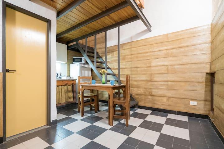 plata baja: cuenta con una mesa para que se puedan sentar 3 personas. una pequena cocina , el bano y una cama simple.