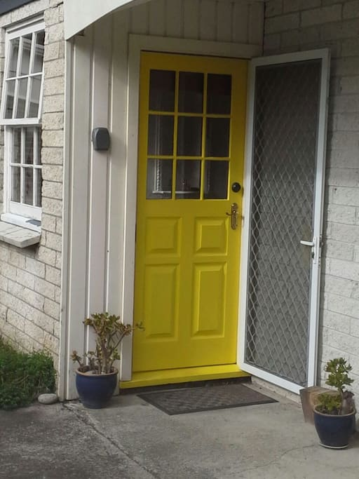 Shared entryway through the yellow door.
