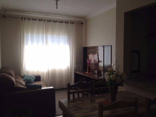 Sala com sofá retrátil e um sofá cama, mesa com quatro cadeiras para um delicioso café
