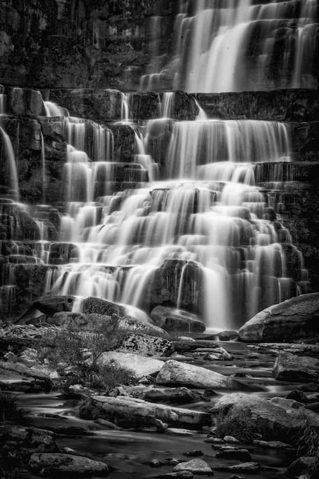 """Chittenango Falls is same height as Niagara Falls:  ~167 feet.   Technically the """"most complex"""" waterfalls in the entire world per vertical foot: Each time the water makes a splash it is called a """"veil"""" (like a wedding veil). More veils (including veils behind veils) than any other falls in the world for this height. Walk down the driveway and across the park.  Look over the top:  5 minutes away!   Walk to the bottom and stand on the bridge:  5 more minutes down rocky path.   Stop half-way down for another great view."""