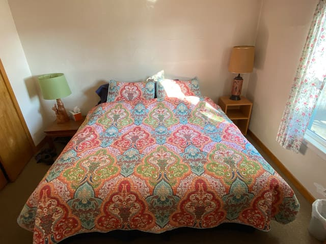 King bed and dressers in second downstairs bedroom. Bathroom with tiled walk-in shower, laundry down the hall