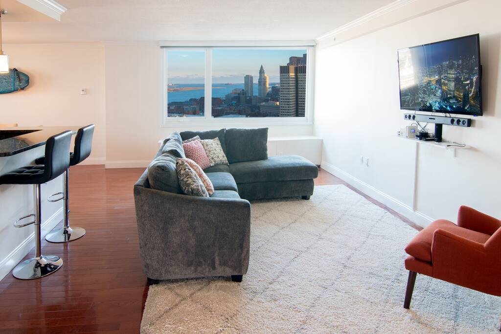 Open-plan living room with incredible view of Boston Harbor and downtown
