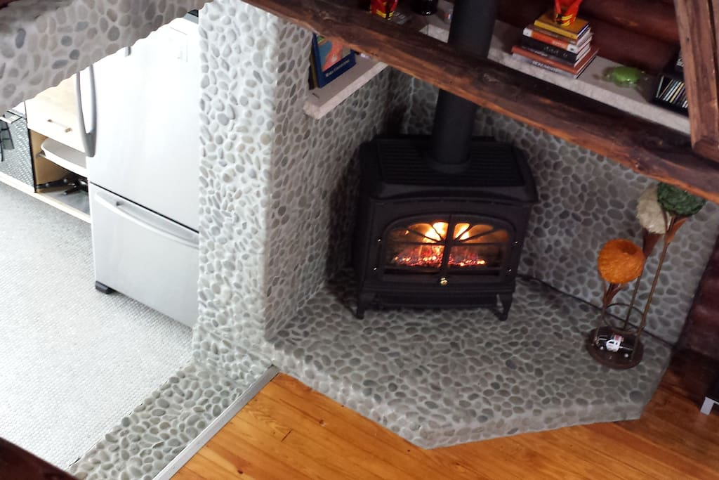 Gas fireplace on stone hearth. Stainless fridge