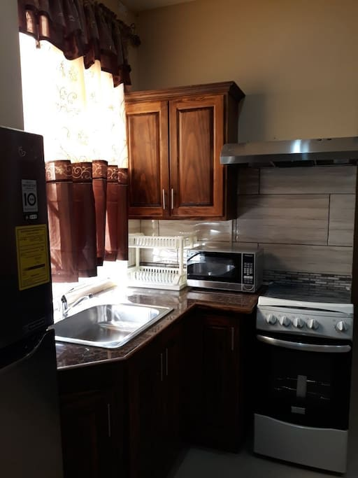 kitchen area equipped with Utensils for 2,Dishring, Guest,Microwave,Stove,Range, Non Frost Refrigerator