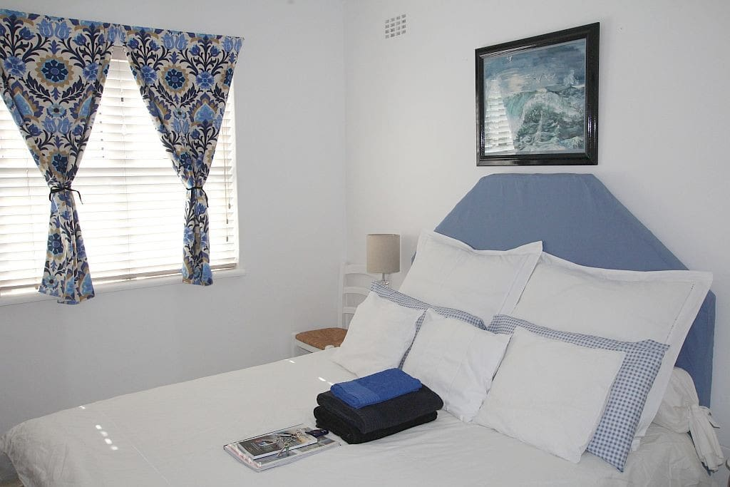 Guest bedroom with towels and a guide or manual. Queen sized bed