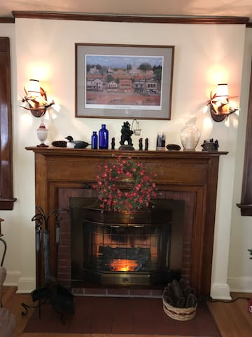 Beautiful cherry mantle fireplace with electric insert in the living room.    Deer antler scones flank the mantle.