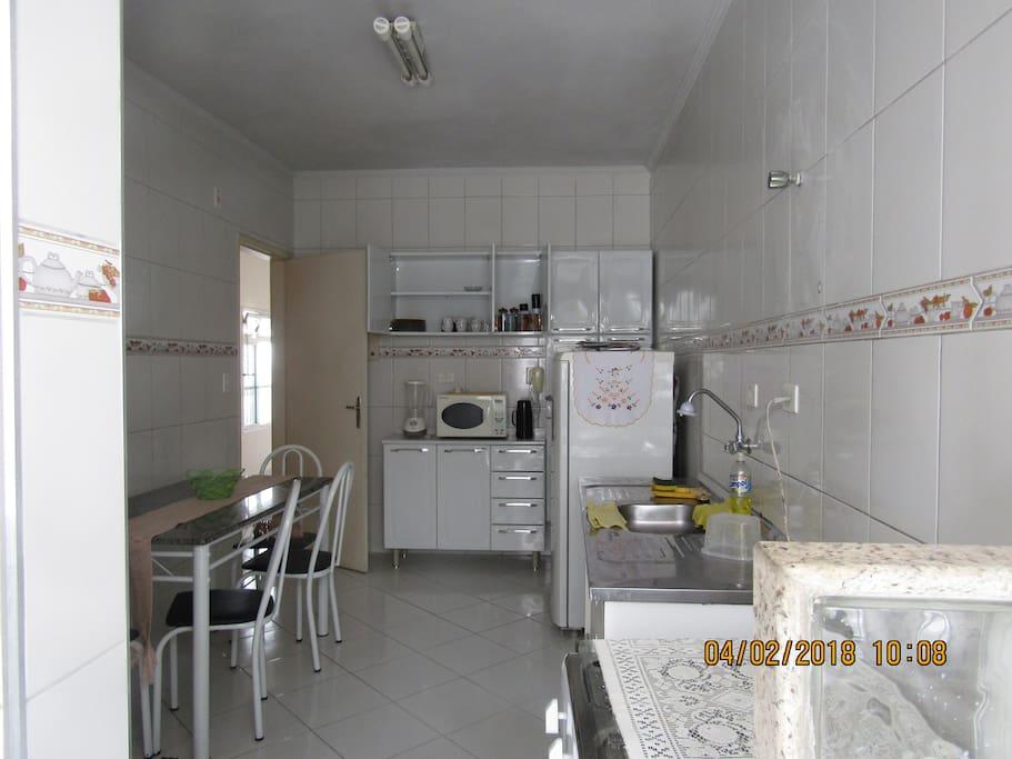 Cozinha com fogão,geladeira micro-ondas, liquidificador, pratos, copos, panelas e talheres.