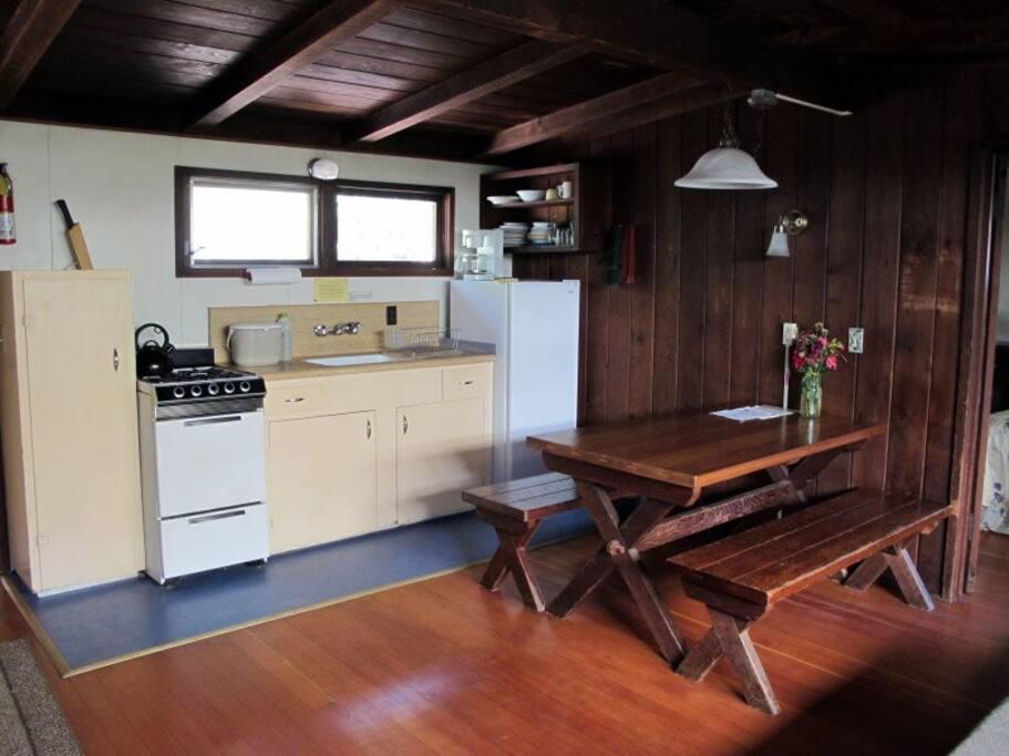Kitchen has oven/range, fridge, sink and utensils.