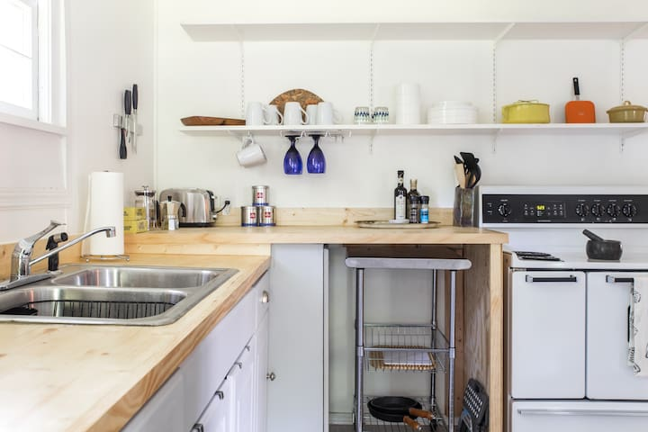 Simple but effectively-appointed kitchen, with open shelving, Henckels knives, Italian and Danish (Dansk) cookware, and multiple espresso + coffee-making options. (Recently added a microwave as well.)