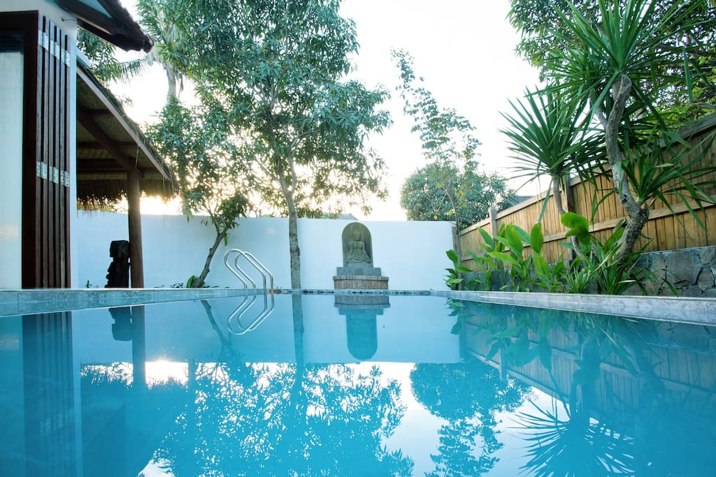 Swimming pool with traditional well and Buddha