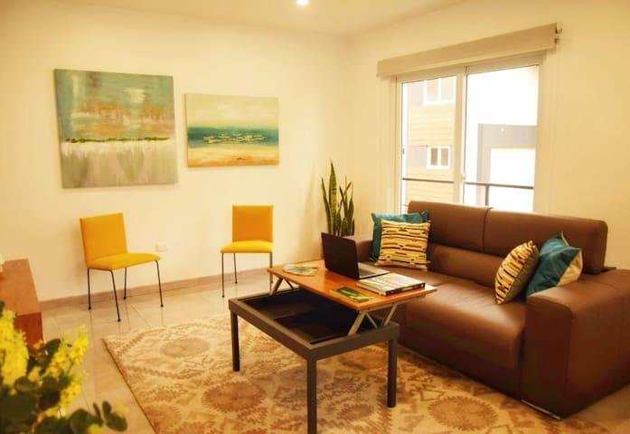 Sala, con mesa de centro convertible a escritorio/ Living  Room with a desk