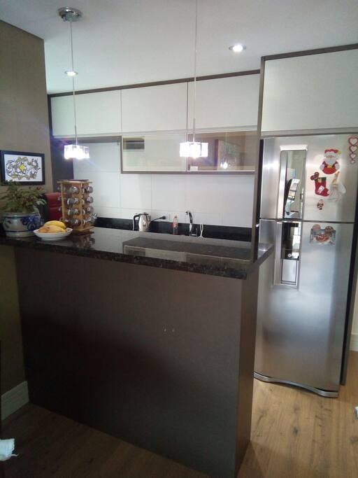 Vista da sala para a cozinha: bancada multiuso e geladeira duplex.