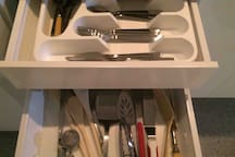 Silverware is in the inner drawer found inside the top drawer. Cooking tools and other kitchen supplies are also provided.