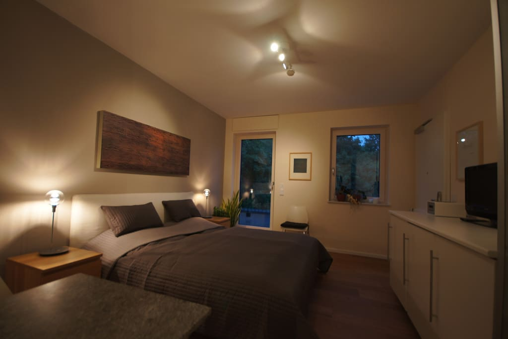 Bedroom at night (16 m²) with kingsize bed, satelit-TV, fridge, coffee maschine and private balcony