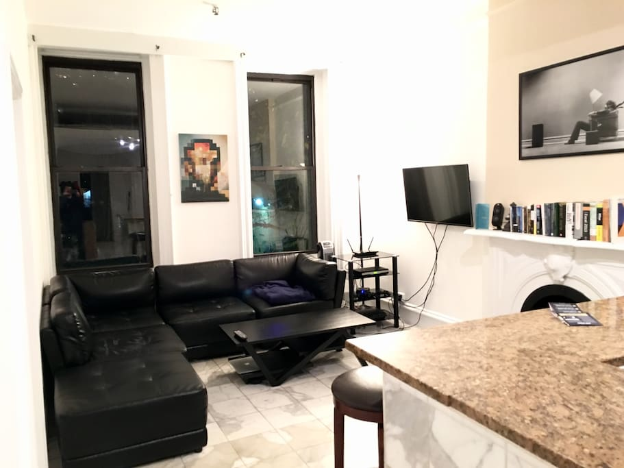 Living room with plush leather couch and TV (cable included)