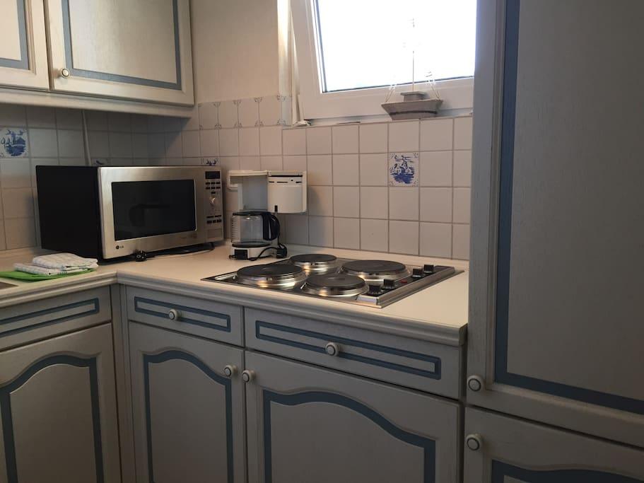 Küche mit 4-Platten-Herd, Backofen-/Mikrowellen Kombi, Kühlschrank mit *** Gefrierfach und reichlich Geschirr/Besteck