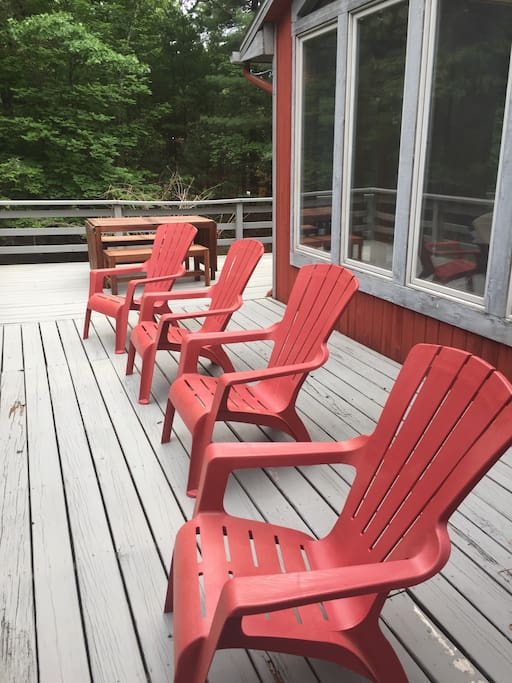 Relax and unwind from the wraparound deck overlooking front yard. Picnic table in background has folding leaves which allow it to expand into seating for al fresco dinng for up to 12