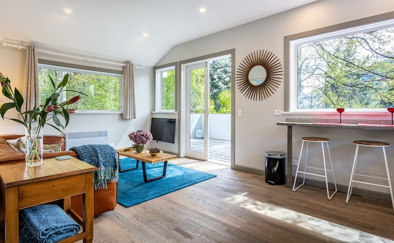 Open plan living room and kitchen open up to the huge private deck. Views over the garden and Queenstown's Shotover River. Take a spin on the Shotover Jet boat ride, it's super fun!