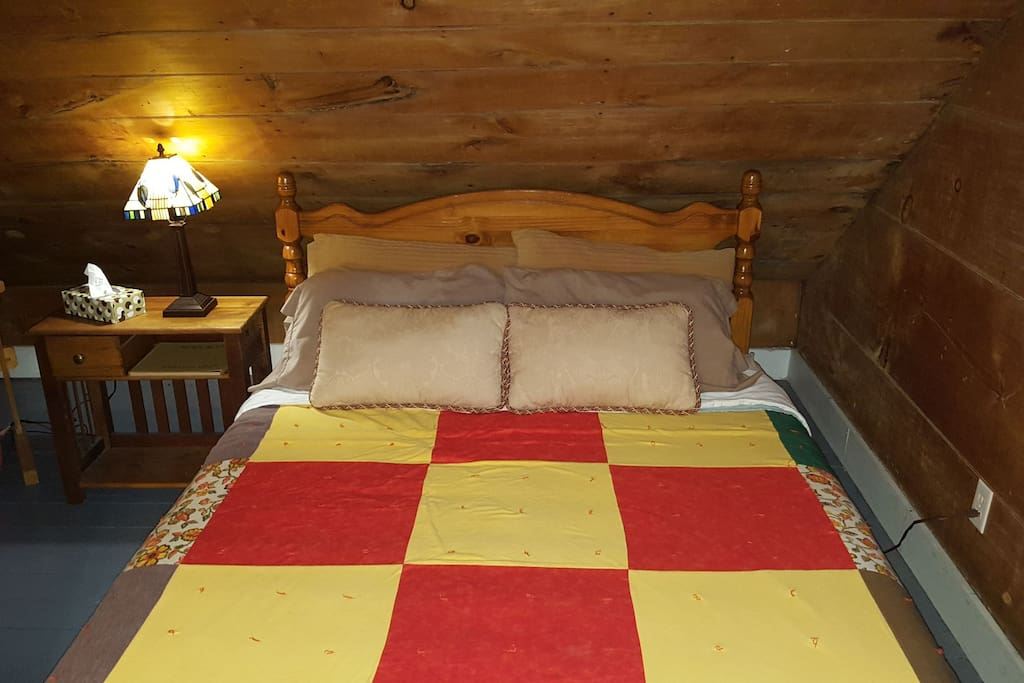 Queen size bed adorned with hand stiched quilt.