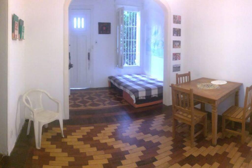 Sala de uso comum, com wifi, mesa de jantar, sofá-cama de casal e ventilador. Iluminada e arejada, com janelas amplas que dão para quintal externo e portas para ambos os quartos, corredor e cozinha.