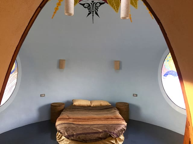 Bedroom 1 with 1-3 queen size oval beds.  2 round mosaic window seats to sit in to plan your day and a gorgeous Butterfly mandala on the ceiling around the skylight