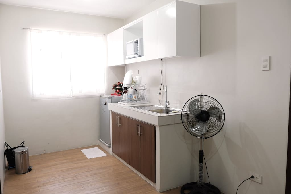 Small kitchen with fridge, microwave, water pot, plates, glasses & utensils you can use