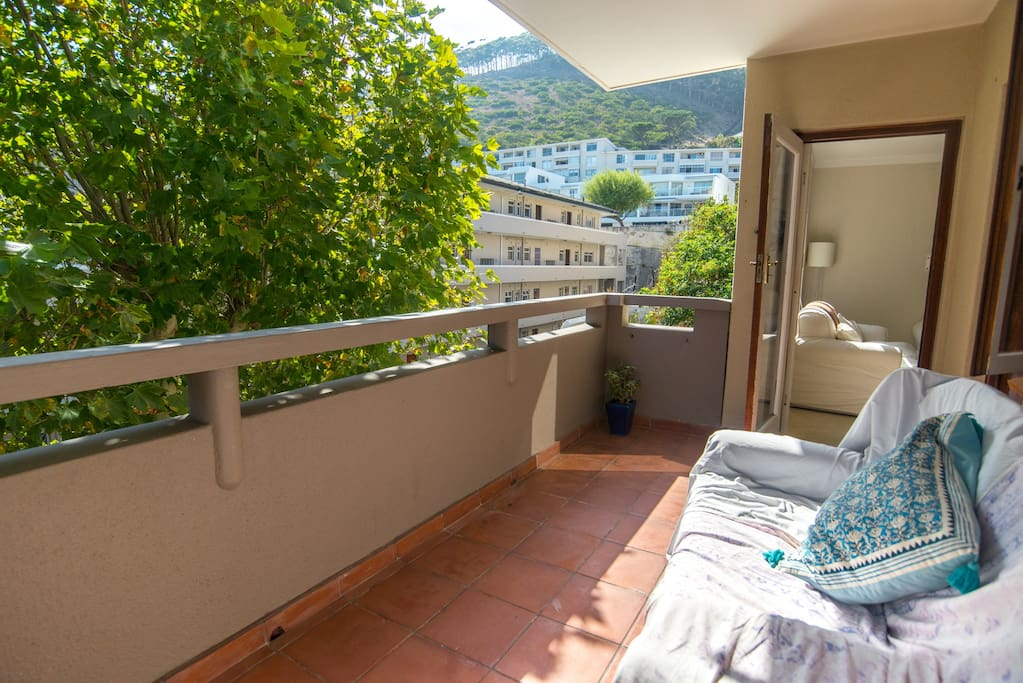 Our large, sunny balcony has two comfortable couches (perfect for afternoon naps), a big tree outside and nice views of Signal Hill (with a tiny bit of sea view on the other side of the balcony).