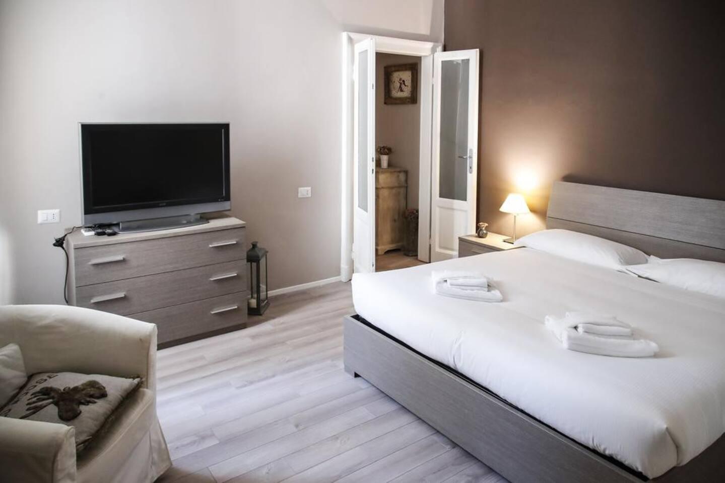 Bedroom: king size bed, intern details, 2 armchairs,  wardrobe, smart TV. Camera da letto: letto matrimoniale, dettagli interni, 2 poltrone , guardaroba, smart TV.