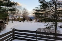 View of frozen pond and rolling hills off the deck in the winter