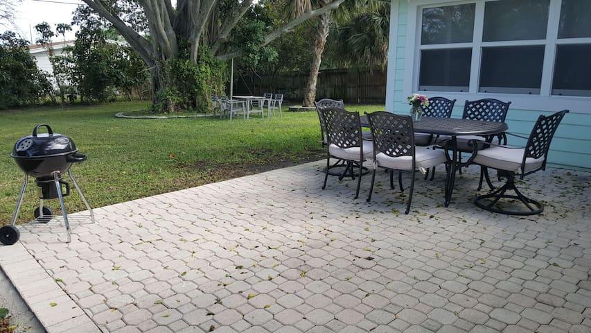 back patio with small BBQ & comfy outdoor table overlooking large yard