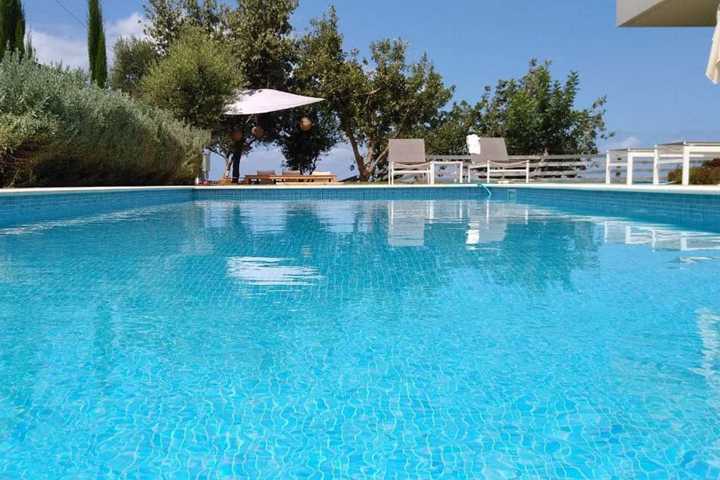 40 sq. m ecological swimming pool surrounded by sun beds and umbrellas.