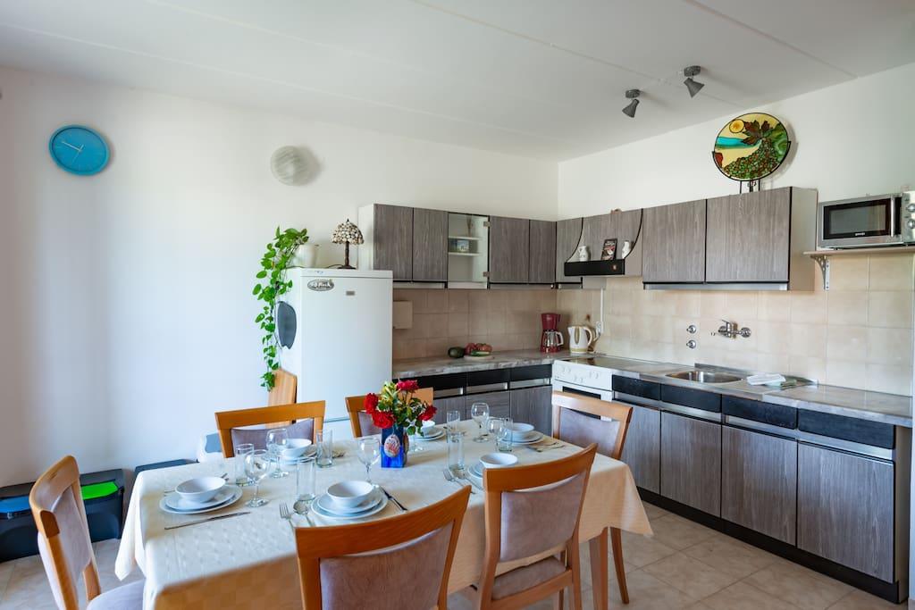Full kitchen with large fridge-freezer combo.
