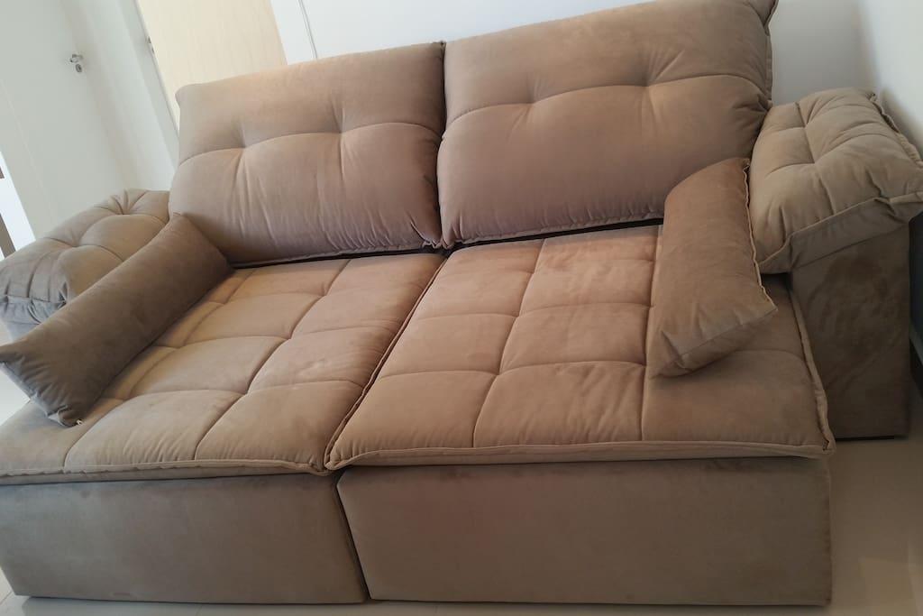 Um sofá enorme retrátil onde podem dormir 2 pessoas tranquilamente